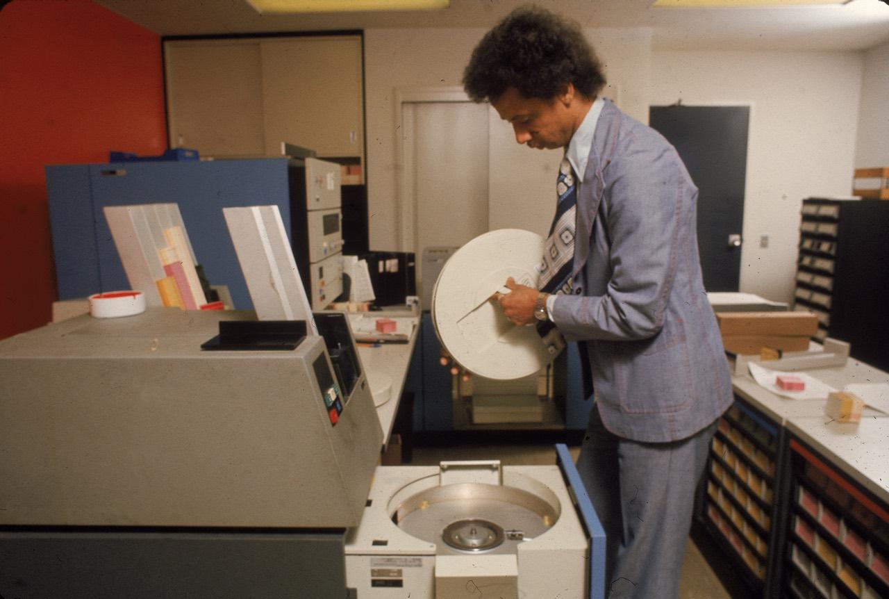 На фото: сотрудник офиса, меняющий съёмный пакет магнитных дисков в офисном компьютере, середина 70-х годов прошлого века.
